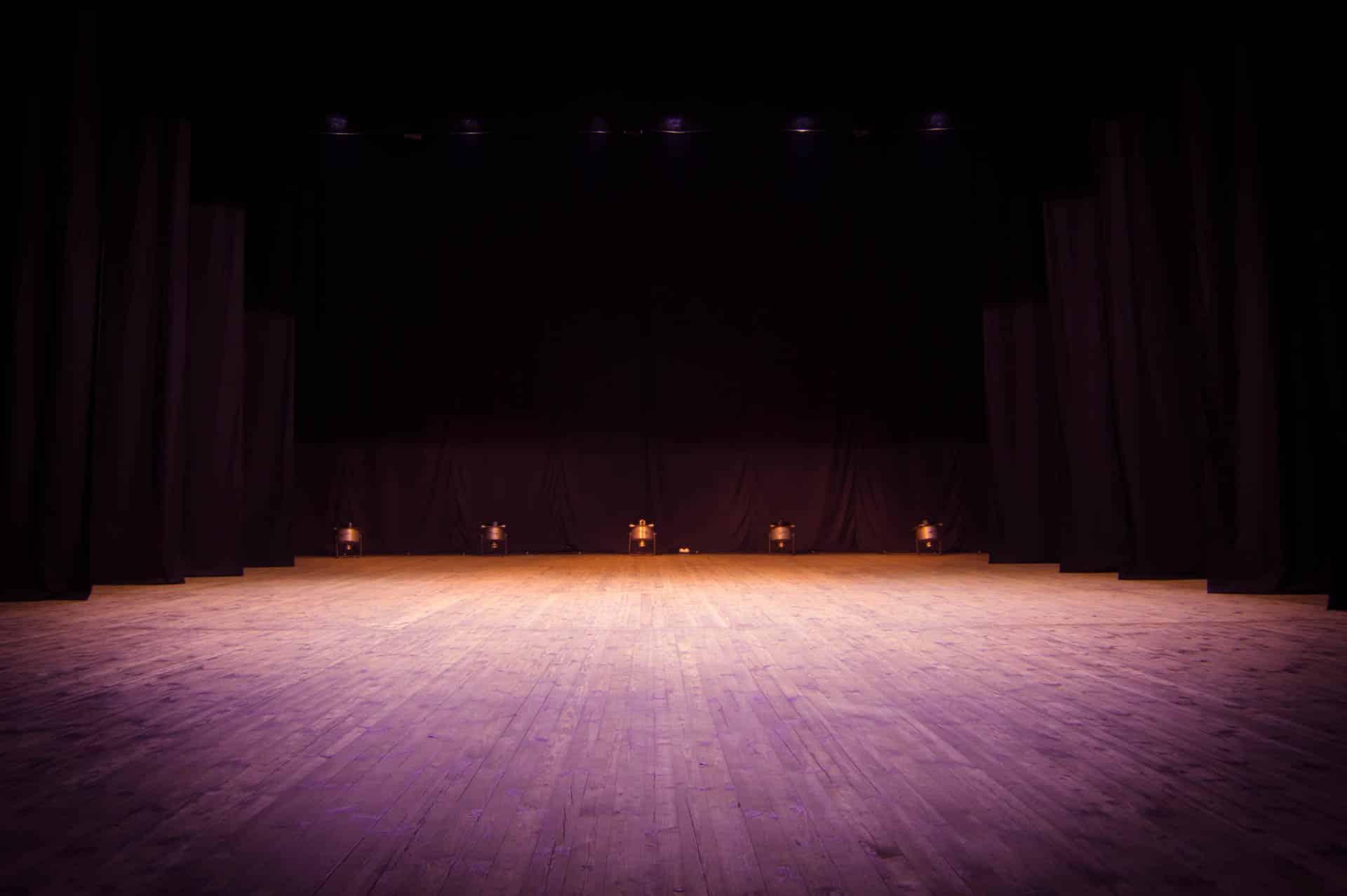 Eine leere Theaterbühne, die vor der Aufführung von Scheinwerfern beleuchtet wird