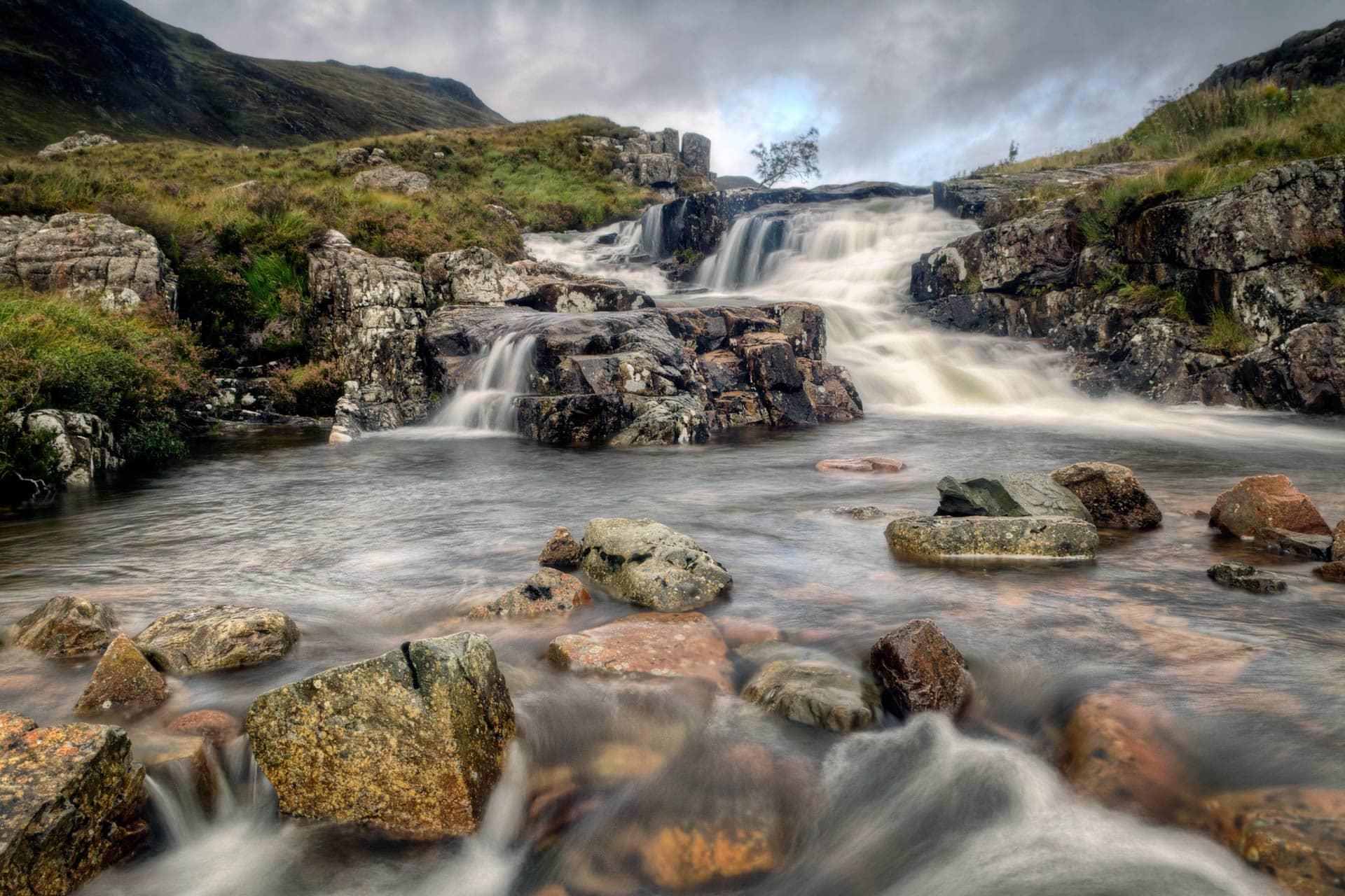 A stream tumbles down the mountainous hillside across rustic rock in Glen Coe, Glasgow.