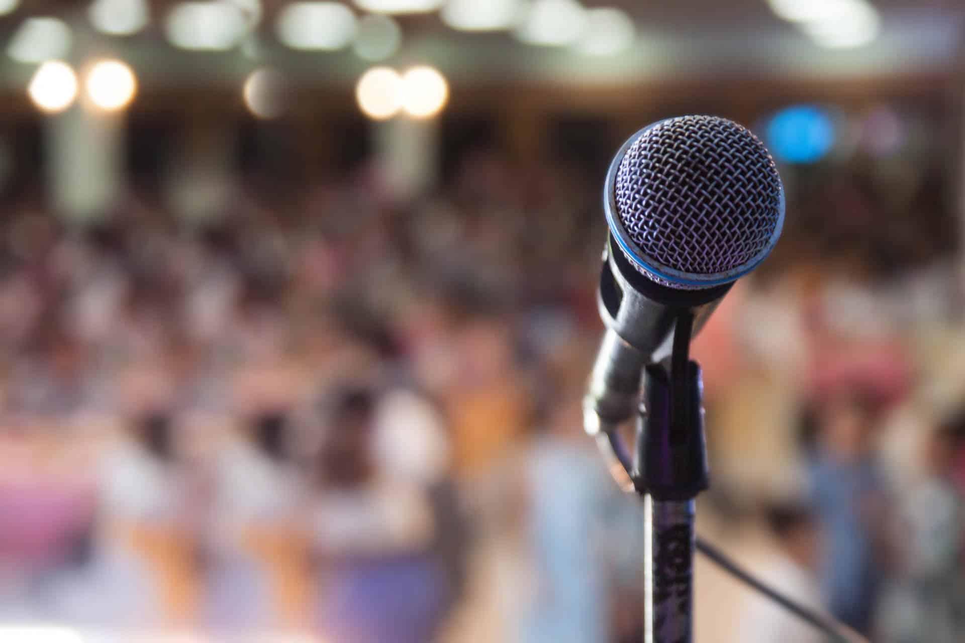 Nahaufnahme eines Mikrofons mit einem unscharfen Publikum im Hintergrund