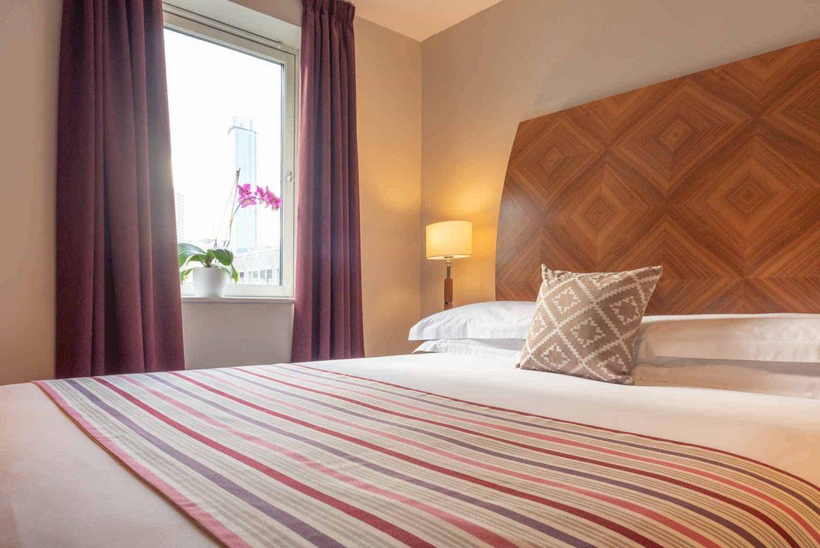 Comfortable bed with crisp white sheets at PREMIER SUITES Birmingham