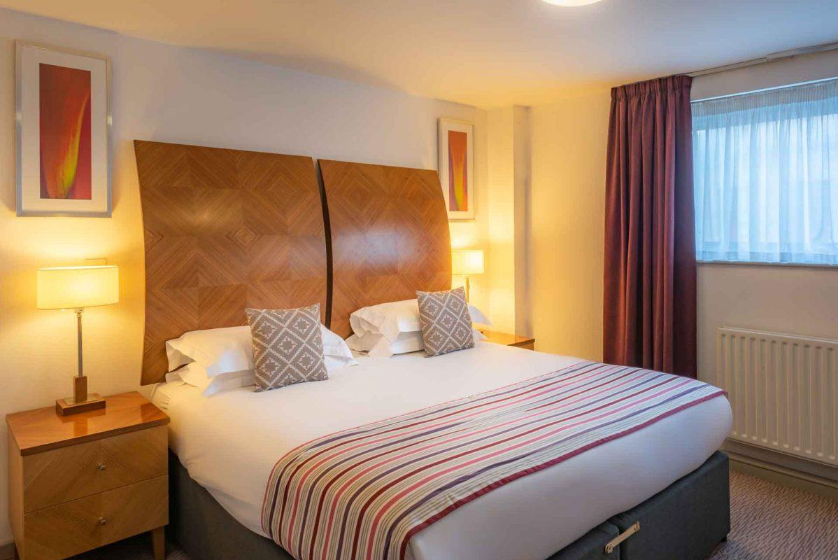 Großes Schlafzimmer mit Tageslicht und bequemem Bett im PREMIER SUITES Newcastle