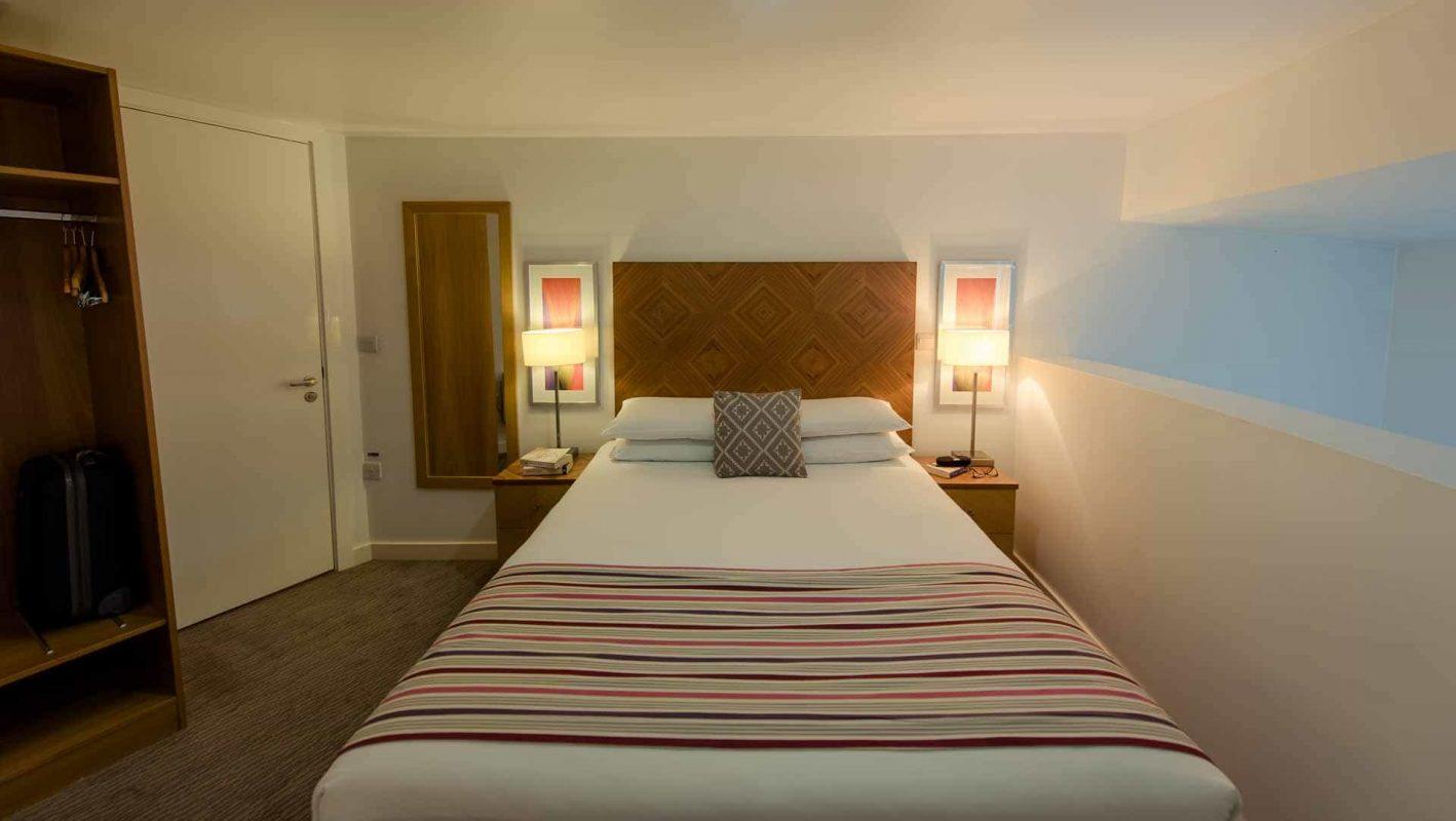 Grand lit double avec deux lampes de chevet allumées à PREMIER SUITES Liverpool