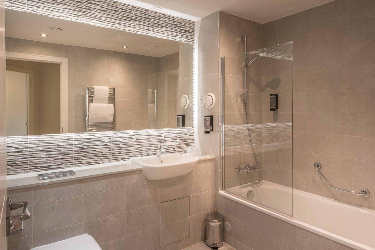 Modern bathroom with bathtub and overhead shower at PREMIER SUITES PLUS Glasgow Bath Street