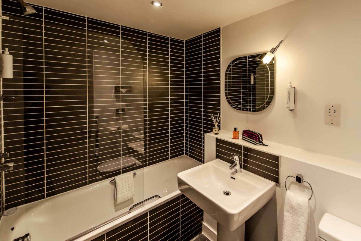 Salle de bain moderne avec carrelage noir à PREMIER SUITES Liverpool