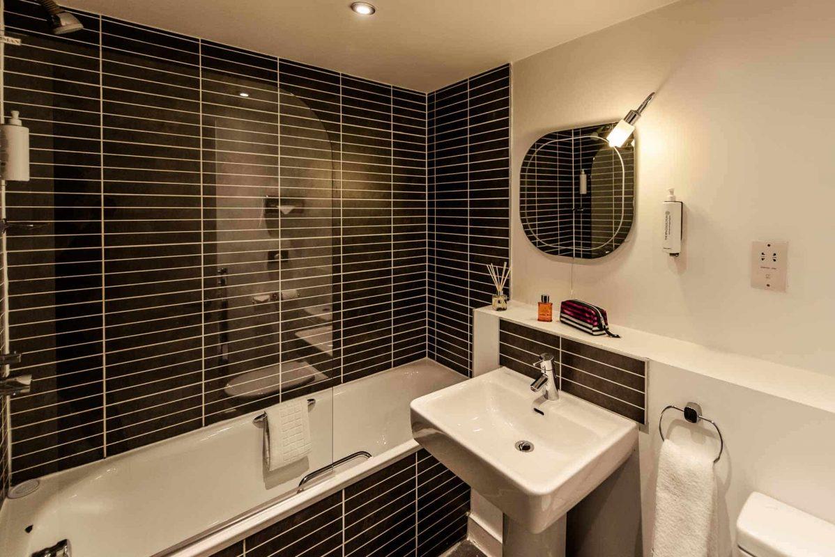 Modern bathroom with black tiles at PREMIER SUITES Liverpool