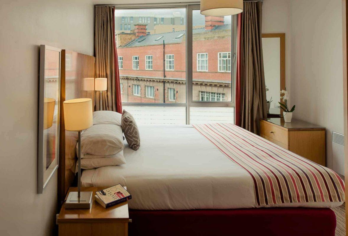 Vue latérale du lit au PREMIER SUITES Liverpool, rempli de lumière naturelle.