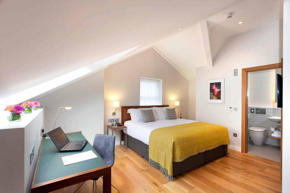 bedroom & work desk in loft style suite with flowers
